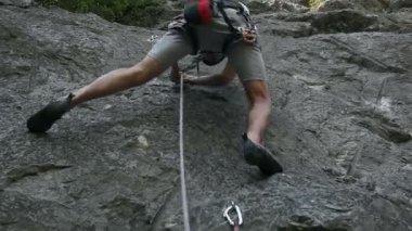 Young man rock climbing in nature shot from below — Vídeo de Stock