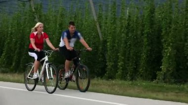 Young couple cycling in the country of hops — Stockvideo