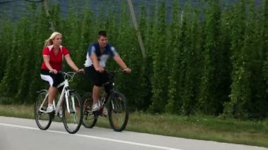 Young couple cycling in the country of hops — Vídeo de stock