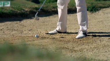 Shot of a man golfer on a sand golf course preparing for hits — Stock Video