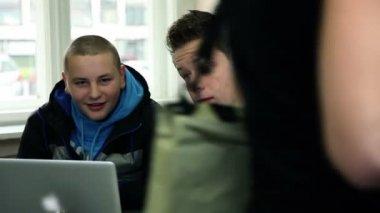 Deux étudiants en parlant et en regardant d'ordinateur à la cafétéria de l'école — Vidéo