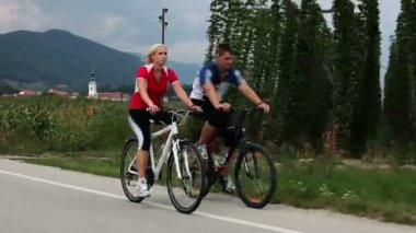 Young couple cycling in countryside — Vídeo de stock