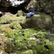 Shot of woman sitting on the rocks covered with moss — Stock Video #28360273