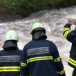 Wiew of firefighters checking the increased mudy and restless river — Stock Video