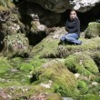 Shot of woman sitting on the rocks covered with moss — Stock Video #28362003