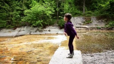 Shot of little girl throwing stones in river — Stock Video