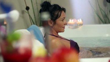 Shot of an older woman soaking in jacuzzi in a fancy hotel — Stock Video