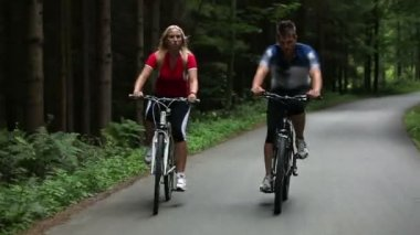 Total of young couple cycling in woods — Vídeo de stock