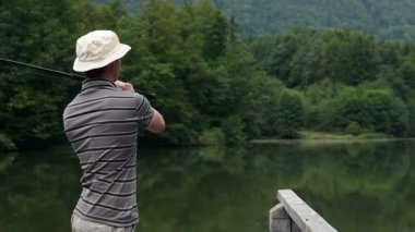 Young man fishing in a beautiful nature — Stock Video