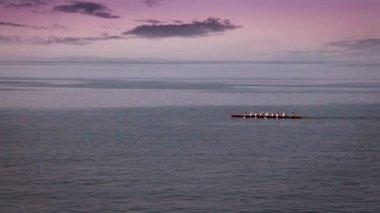Inquadratura panoramica della squadra che è remi in barca sul mare con qualche bel nuvole nella parte posteriore — Video Stock