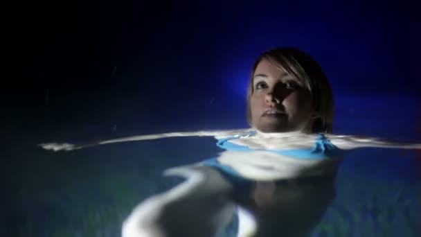 Foto de una mujer joven y bonita en bikini azul que disfruta en la piscina al aire libre en la noche — Vídeo de stock