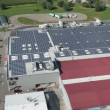 Panorama slide shot from helicopter representing an industrial part of a small town with roofs covered with solar power stations — Stock Video #28398233