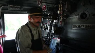 Shot of the stoker on a steam engine driving the train — Stock Video