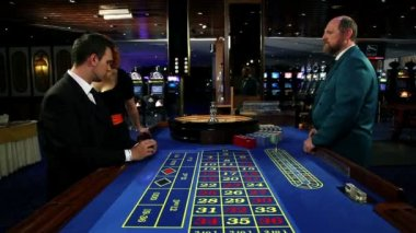 Young and attractive woman whispering to a man while he is about to bet at roulette in casino — Stock Video