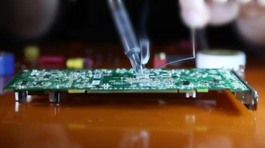 Shot of a man solder a chip on a graphics card — Stock Video