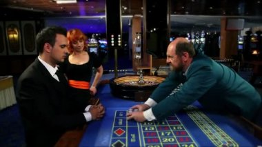 Young man receiving winning chips and giving one to his mistress and another one to casino worker — Stock Video