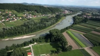 Panorama slide shot from helicopter representing river-bed that slowly passes through a beautiful green valley with small villages beside the river — Stock Video