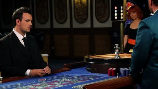 Juegos de azar y el coqueteo detrás de la mesa de ruleta en casino — Vídeo de stock