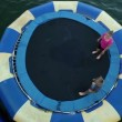 People jumping on trampoline in water — Stock Video