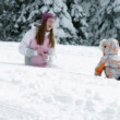 Teenaged girl and young child playing with snow — Vídeo de stock