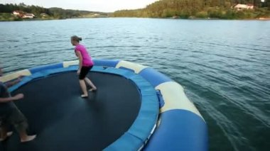 People jumping on trampoline in water — Stockvideo