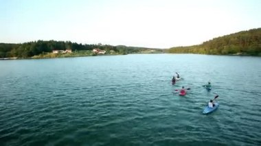 Young people slowly canoeing in the lake — Vídeo stock