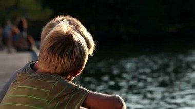 Unga pojkar tittar på sjön och talar — Stockvideo