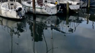 Reflection of sailboats in harbor on cloudy day — Stock Video
