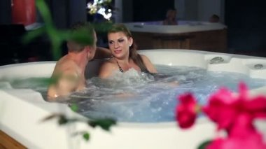Young, romantic couple in jacuzzi spending time together — Stok video