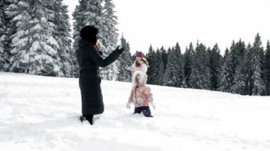 Mother and two children enjoying on snow in idyll — ストックビデオ