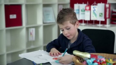 Young boy drawing in kindergarten — Video Stock