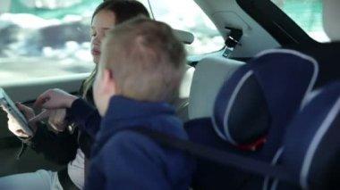 Younger brother and sister arguing over tablet pc while family driving to vacation — Stock Video