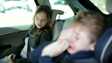 Brother and sister in the back seat of car sleeping while family traveling — Vídeo de Stock