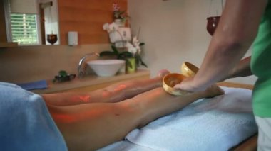 Tapping massage on woman legs with coconut shell — Stock Video