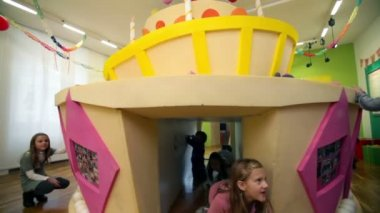 Young boys and girls in kindergarten playing with huge birthday cake — Stock Video