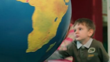 Young boy turning around big Earth globe — Stock Video