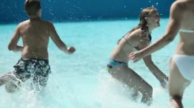 Young people running in to pool having fun — Stock Video