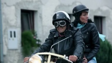 Following middle-aged couple on old motorcycle driving through town — Stock Video