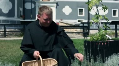 Medium shot of monk picking herbs in front of monastery — Stock Video