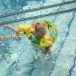 Little boy with water wings in pool — Stock Video