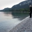 Woman throwing rocks in to sea at dawn — Stock Video #37041493