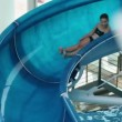 Young girl sliding down the waterslide — Stock Video