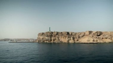 Wide shot of rocky cliffs with lighthouse at tourist resort in Egypt — Stock Video