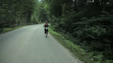 Tracking woman running through forest road — Stock Video