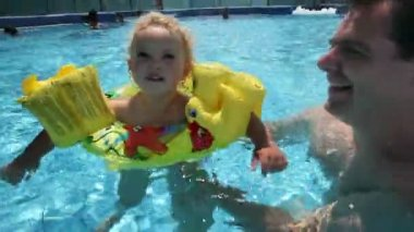 Crane shot of little kid with father enjoying pool — Stock Video