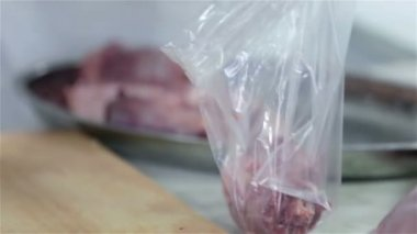 Close up of putting pieces of meat in to bag — Stock Video