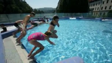 Kids jumping into pool in outside environment — Stock Video