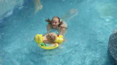 Girl and her younger brother having fun in pool — Wideo stockowe