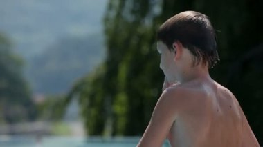 Young boy preparing to jump in to pool water — Video Stock