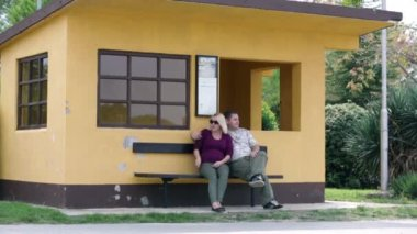 Couple sitting on bench in front of orange house — Stock Video